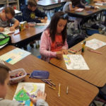 Elementary students work on an art project with an Artists in the Classroom teacher.
