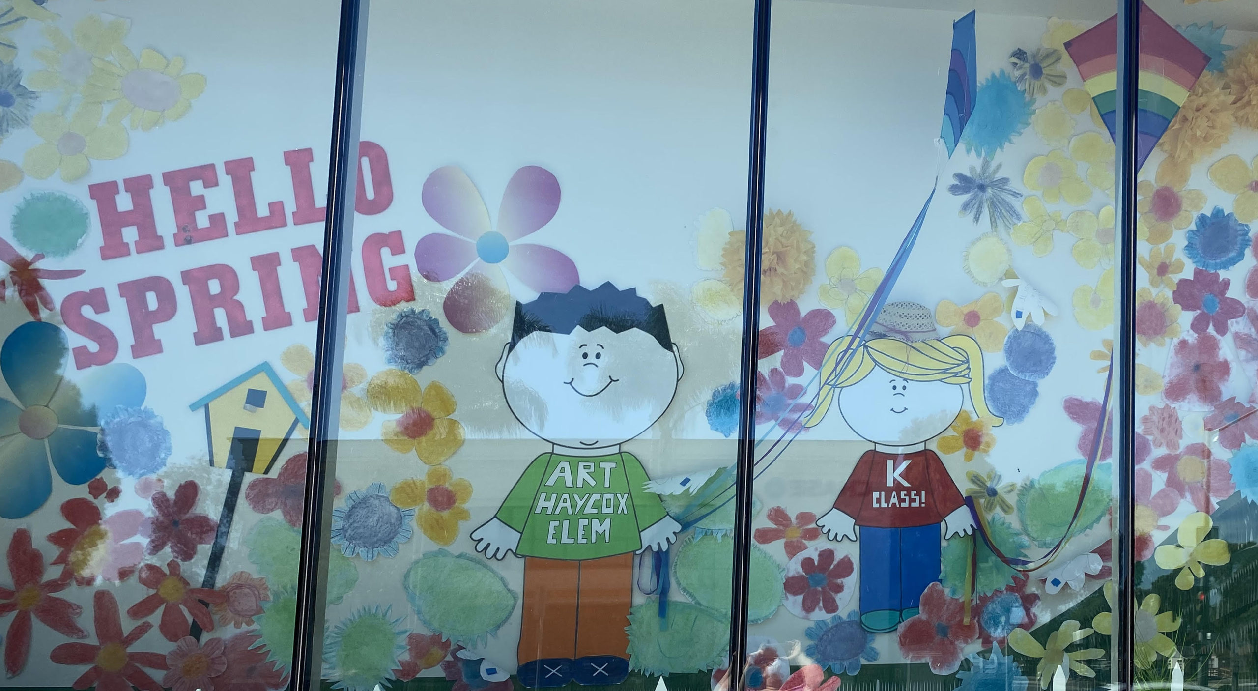 A public art display of work made by elementary school students hangs in the window of a commercial property in Ventura.